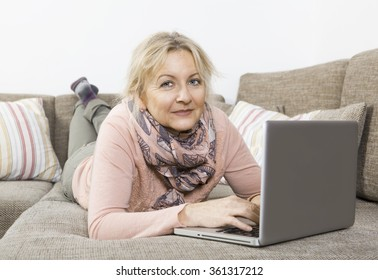 an older blonde woman lying on the sofa and working with a laptop