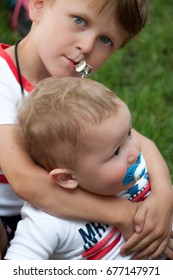 An older boy is holding a younger child proactively. The older child has a whistle in his mouth and the baby has a pacifier in his mouth. The older boy is looking directly at the camera. Best friends