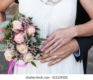 older bride and groom hands and rings with flowers
