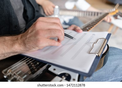 Older brother explains to his younger one how to use notes on music sheets on an exapmple