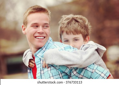 Older brother giving young boy a piggyback ride outdoors smiling