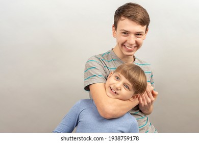 The older brother grabs his brother by the neck and throws him back.