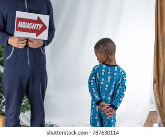 Older brother holding up sign towards toddler brother indicating he is naughty as he throws a tantrum.