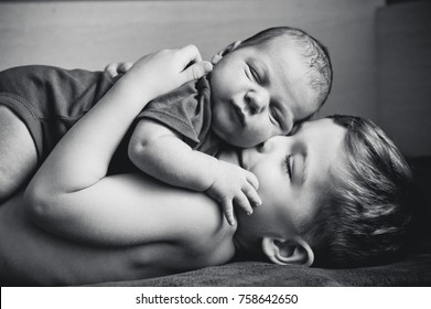 The older brother hugs the younger newborn brother. Love. Black and white photography.