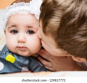 Older brother kissing his newborn baby sister
