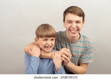 The older brother mocks the younger and strangles him with his hand.