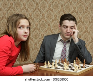 Older brother playing Chess with little sister with no electronics - unpluged and off line