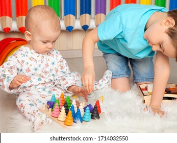 Older brother plays with younger sister in Montessori toys in the children's room. He helps the baby to take a wooden toy Christmas tree. Montessori pedagogy. Development of preschool children.