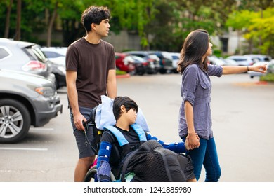 Older brother and sister pushing disabled little boy in wheelchair across parking lot