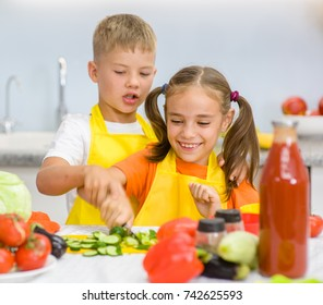 older brother teaches her sister to cut vegetables for lunch