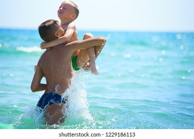 Older brother teenager plays with younger brother at sea