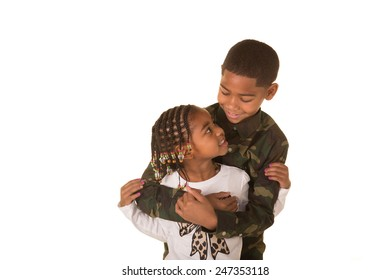 An older brother and younger sister embracing