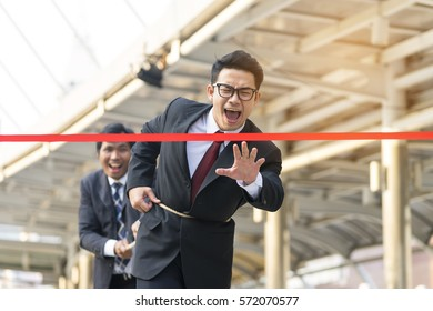 Older business man pulling a rope from waist of younger of businessman, preventing to reach a finish line, race to the business goal - Business competition concept