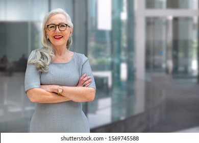Older business woman CEO standing and smiling confident, successful, at office building with copy space