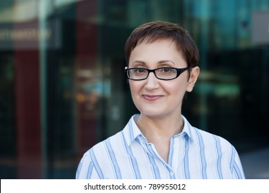 Older business woman headshot. Close-up portrait of executive, teacher, principal, CEO. Confident and successful middle aged woman 40 50 years old wearing glasses and shirt and smiling