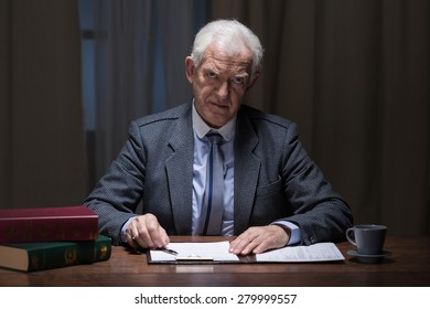 Older busy man working late at night in his cabinet