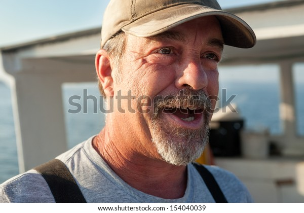 Older, caucasian, bearded Lobster fisherman talking and looking off to the side, Maine, USA