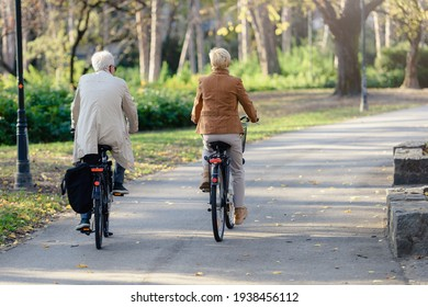 Older Caucasian couple riding bicycles through public park together. Back view