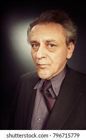 Older caucasian man in bad dressed suit on black background