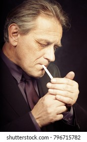 Older caucasian man lighting cigarette on black background