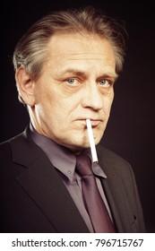 Older caucasian man smoking cigarette on black background