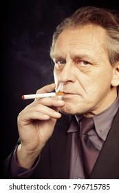 Older caucasian man smoking electronic cigarette on black background