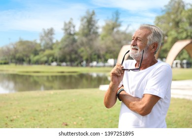 Older caucasian men, white beard in white shirt and blue jean with sunglasses is resting and living after retirement in the park during the summer. He looking or thinking something.