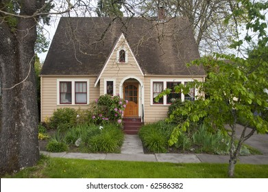 Older clapboard bungalow surrounded by green shrubs