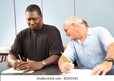 Older college student trying to copy off a younger student's test paper.