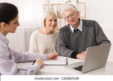 Older couple considering new home purchase talking with real estate agent and looking at laptop