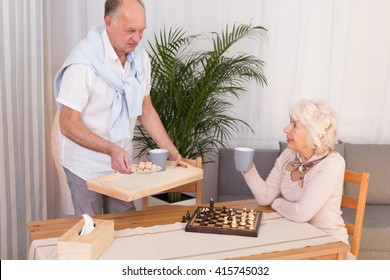 Older couple having break for tea and cookies during little home chess contest