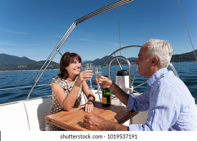 Older couple having champagne on boat