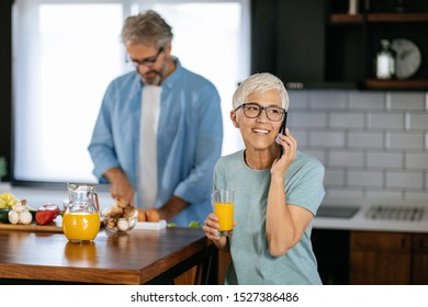 Older couple in the kitchen. Man is preparing some food, while his wife is telephoning