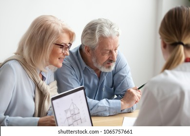 Older couple reading contract at meeting with real estate agent considering new home purchase, realtor or bank worker consulting senior family about buying house loan with project plan on laptop