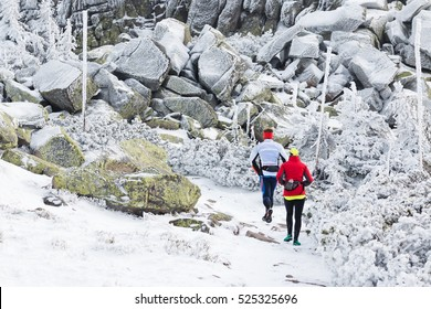older couple running together on winter mountain trail covered with snow in freezing temperatures