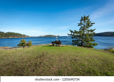 An older couple sitting on a wooden bench looking out to the ocean and islands on a sunny summer day at Drumberg Provincial Park on Gabriola Island, British Columbia, Canada