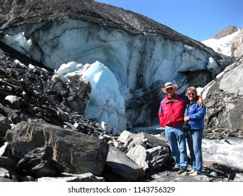 Older couple stand in front of the Worthington Glacier in Alaska.  The man is wearing a red jacket and the woman a blue.