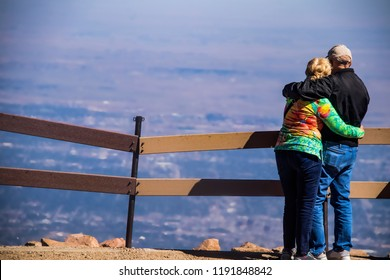 An older couple stand with their arms around each other at the sumit of a mountains looking down at a panoramic view