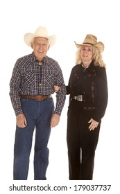 An older couple standing side by side in their western hats.