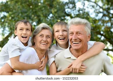 Older couple standing with their grandchildren in summer park