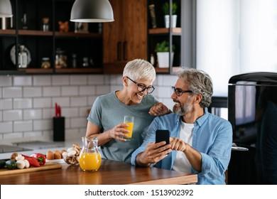 Älteres Ehepaar benutzt Handy bei einem gemütlichen Frühstück in der Küche