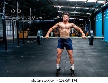 older defined muscular man olympic lifting in gym