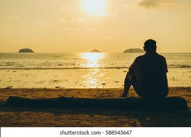 Older depressed man, sunset at beach