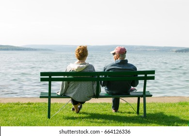 An older elderly retired couple sit on a park bench casually dressed looking at a view of a beautiful lake. Concept shot for retirement and late life.