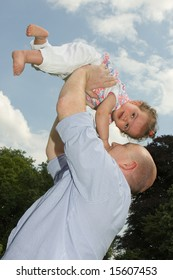 Older father playing with his little girl in the park