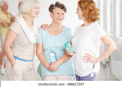 Older female friends with water bottles talking before aerobics classes