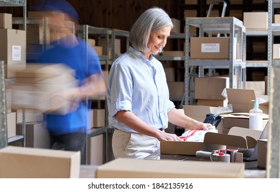 Older female small business owner worker packing post shipping ecommerce retail order in box in warehouse with courier hurry in blur motion to deliver parcels. Fast speed express rush delivery concept
