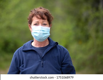 Older female wearing a blue mask for protection.