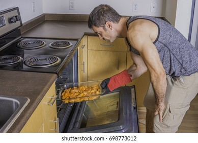 Older fit male putting chicken in the oven