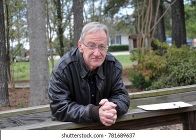 Older gentleman standing on a bridge